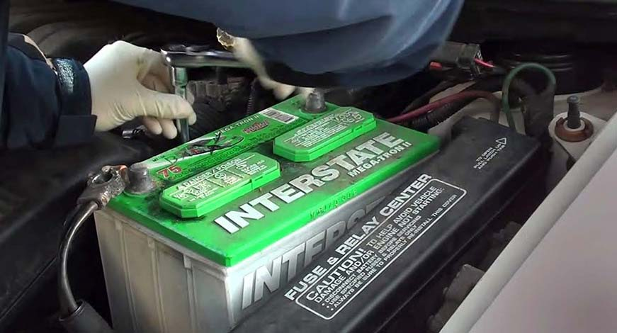 A technician from Interstate Batteries of Las Vegas performing an auto battery installation.