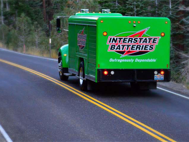 The rear of an Interstate Batteries truck on the highway providing fast battery delivery.